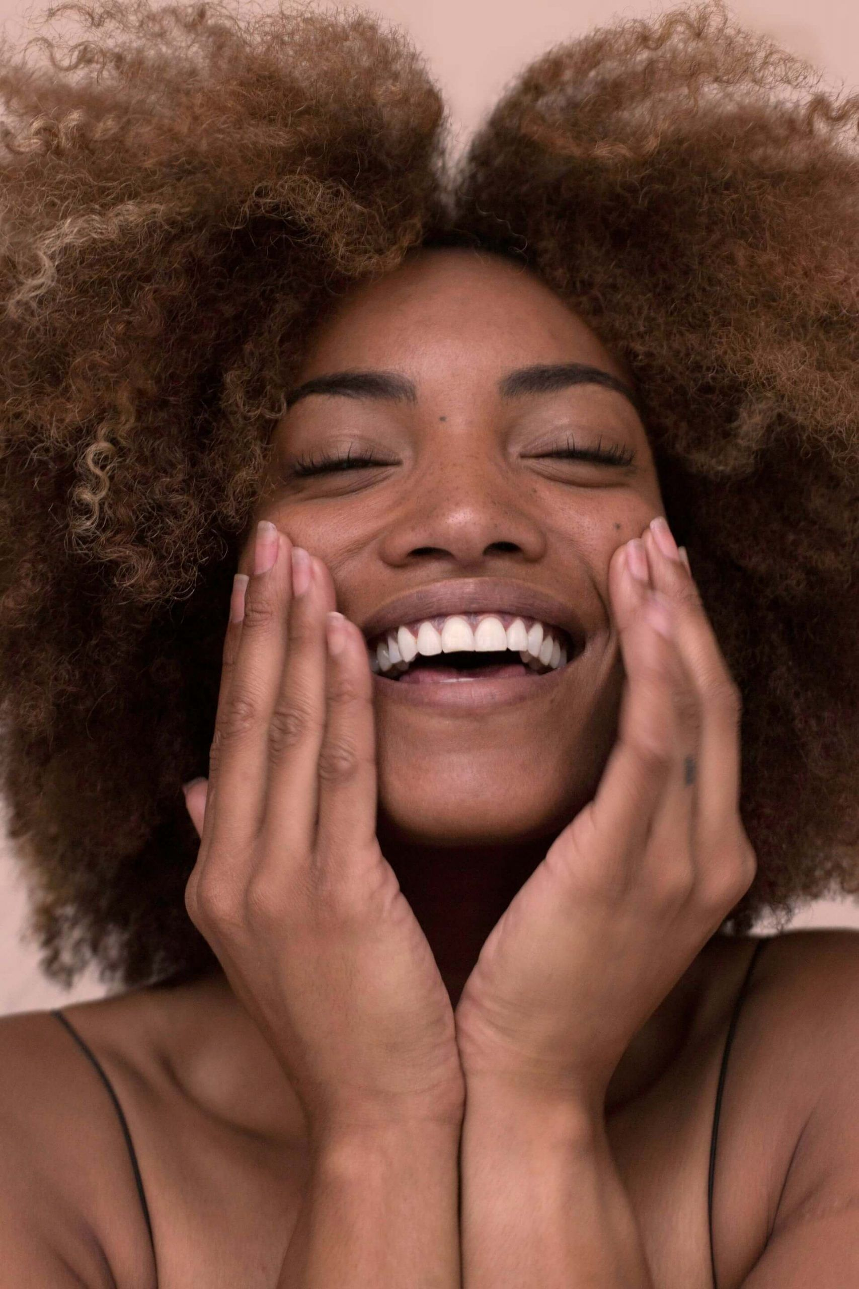 brown girl massaging her face and smiling
